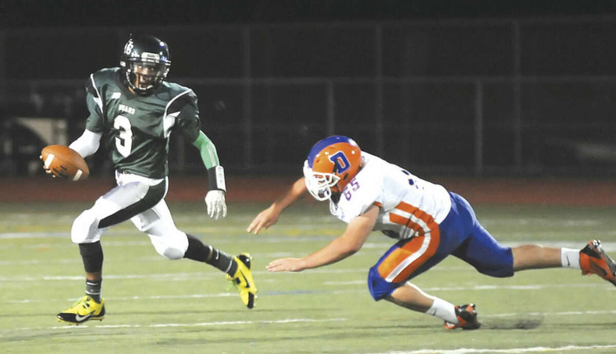 Hour photo/John Nash Norwalk quarterback Jeremy Linton (3) scrambles away from the pursuit of Danbury defender Joey Syryla during Friday's game at Testa Field in Norwalk. Danbury pulled out a 14-6 win.