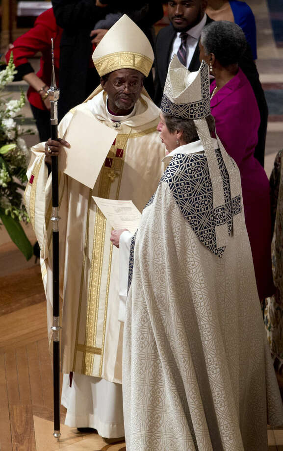 Episcopal Church Presiding Bishop-elect Michael Curry receives the pastoral staff from his predecessor, Presiding Bishop Katharine Jefferts Schori, during Mass at the Washington National Cathedral, Sunday, Nov. 1, 2015, in Washington. Curry, who comes to the job after nearly 15 years leading the Diocese of North Carolina, was elected last summer to succeed Schori, the first woman leader of the church. (AP Photo/Jose Luis Magana)