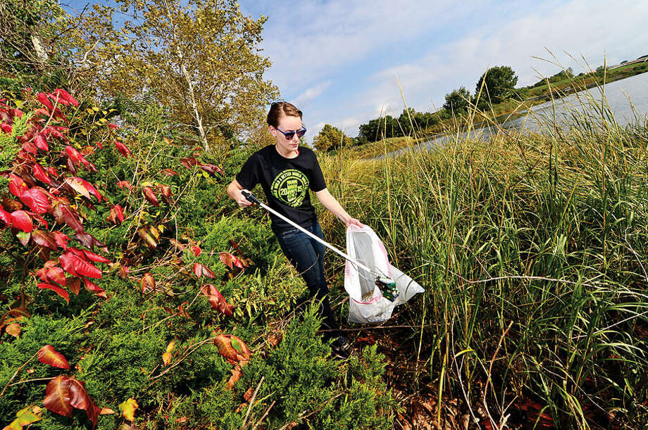 Hour photo / Erik Trautmann Eleanor Thompson of Builders Without Borders picks up trash from the shoreline of the Norwalk River at Oyster Shell Park Saturday as part of the International Coastal Cleanup coordinated in Connecticut by Save the Sound. Save the Sound hosted 17 public coastal cleanups Saturday including one at Oyster Shell Park.