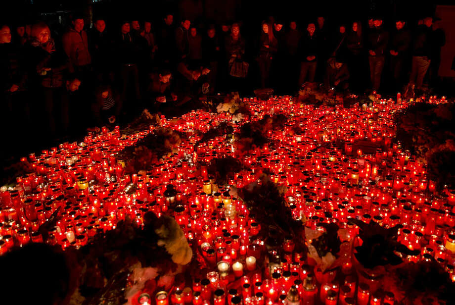 People, lit by burning candles, stand outside the compound that housed a nightclub where a fire occurred in the early Saturday in Bucharest, Romania, to pay respects to the victims, marking 24 hours after the accident Sunday, Nov. 1, 2015. Flames spread quickly through the crowded basement club, trapping many and triggering a stampede, making it the deadliest nightclub blaze in Romanian history. (AP Photo/Vadim Ghirda)