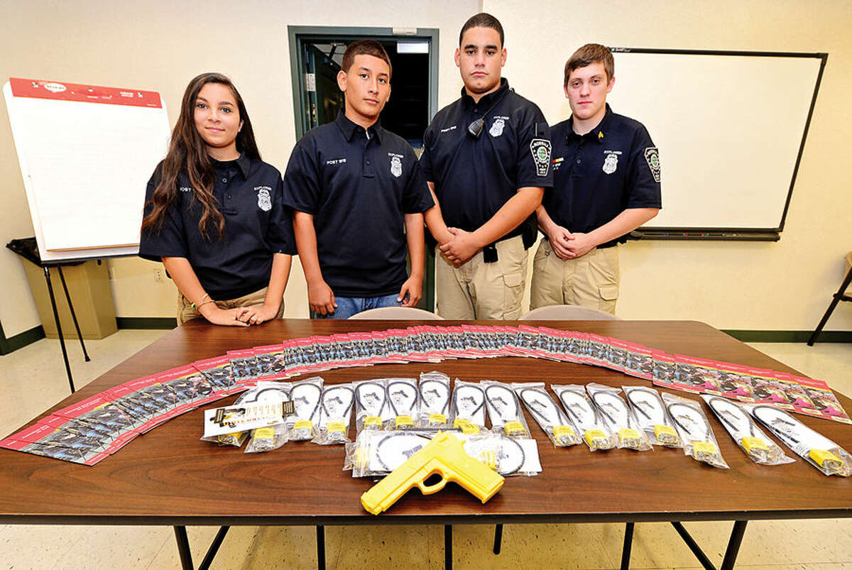 Hour photo / Erik Trautmann The Norwalk Police Explorers Janessa Martinez, Eric Alicea, William Lopez and Noah Velez conduct a Project Child Safe program in the Community Room at the Norwalk Police Department Saturday. The program educates the community on safe firearms handling and storage practices and provides free gunlocks for gun owners.