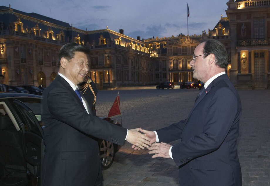 FILE- In this March 27, 2014 file photo, Chinese President Xi Jinping, left, is welcomed by French President Francois Hollande, right, at the Chateau de Versailles, in Versailles, west of Paris, for a concert and dinner. The French President Francois Hollande hopes to give a push to climate talks during a two-day state visit to China, ahead of a global U.N. conference in Paris at the end of the year. (AP Photo/Michel Euler, FILE)