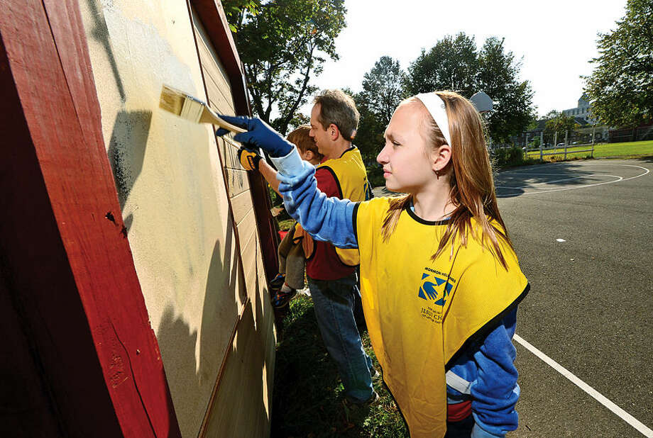 Hour photo / Erik Trautmann Chloe Ashton paints the supply shed at Ryan Park Saturday as part of the local Church of Jesus Christ of Latter-Day Saints annual Day of Service.
