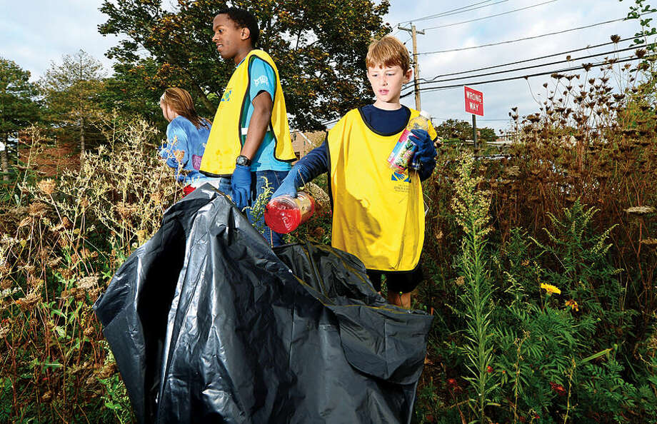 Hour photo / Erik Trautmann 8 year old McKay Miller picks up garbage in the flower garden at Ryan Park Satyrday as part of the local Church of Jesus Christ of Latter-Day Saints Day of Service.