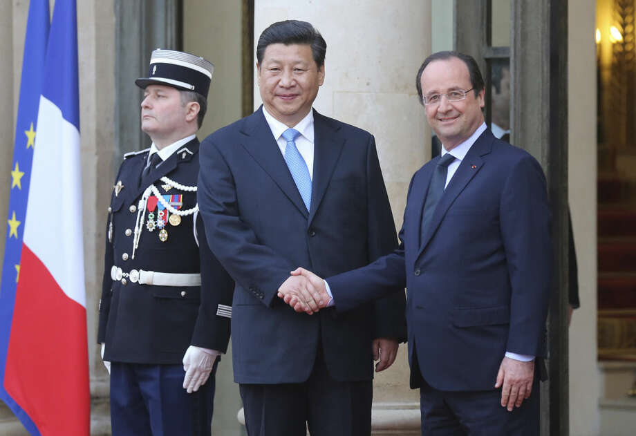 FILE- In this March 26, 2014 file photo, French President Francois Hollande, right, takes leave of Chinese President Xi Jinping following their meeting at the Elysee Palace in Paris, France. The French President Francois Hollande hopes to give a push to climate talks during a two-day state visit to China, ahead of a global U.N. conference in Paris at the end of the year. (AP Photo/Remy de la Mauviniere, FILE)