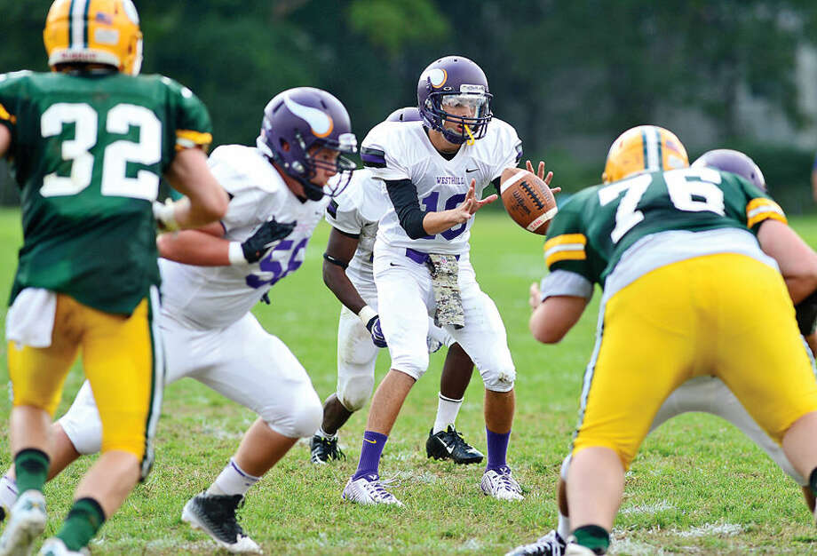 Hour photo / Erik Trautmann Westhill QB Anthony Dastoli receives the snap during their game against Trinity Catholic High School Saturday.