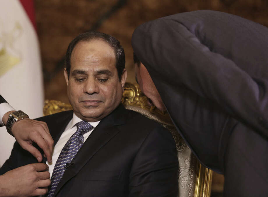 Egyptian President Abdel-Fattah el-Sissi confers with an aide before an interview with The Associated Press at the presidential palace in Cairo, Saturday, Sept. 20, 2014. In his first interview with foreign media since taking office in June, el-Sissi has told AP he is prepared to give whatever support is needed in the fight against the Islamic State group but says military action is not the only answer. (AP Photo/Maya Alleruzzo)