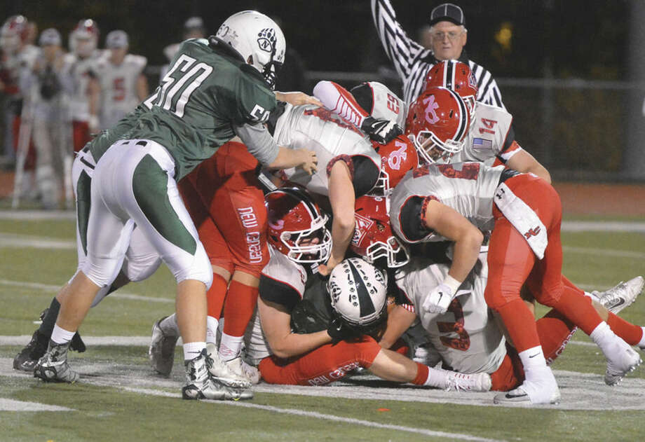 Hour photo/Alex von KleydorffNorwalk's Joey Laracca is tackled by five different New Canaan defenders on Friday night.