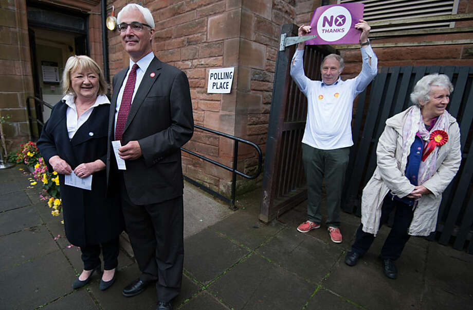 Britain's former chancellor and leader of the Better Together campaign Alistair Darling, second left, and his wife Maggie, pose with NO campaigners in the background, outside the polling station at the Church Hill Theatre, in Edinburgh, Thursday Sept. 18, 2014. Polls opened across Scotland in a referendum that will decide whether the country leaves its 307-year-old union with England and becomes an independent state. (AP Photo/PA, Stefan Rosseau) UNITED KINGDOM OUT NO SALES NO ARCHIVE