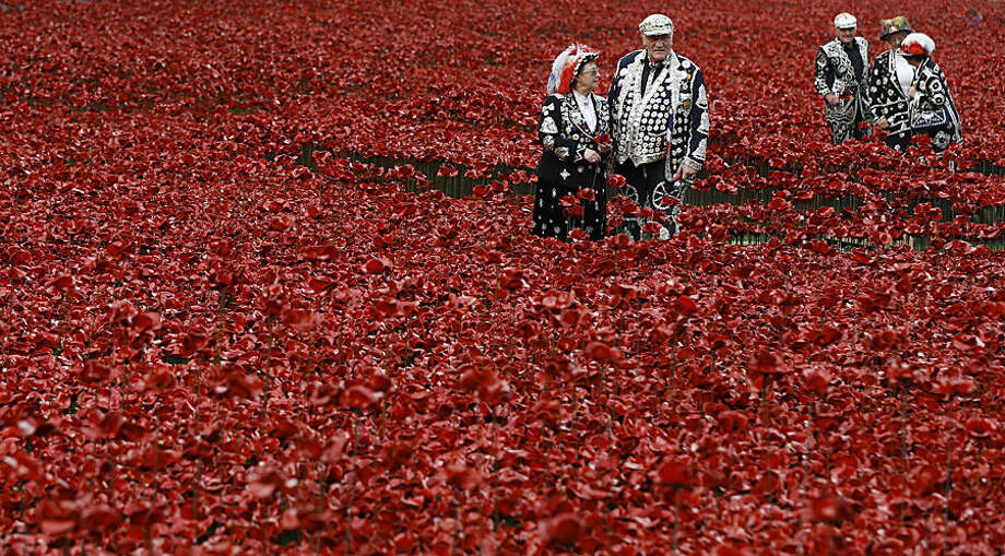 Pearly Kings and Queens plant poppies at the Tower of London in London, Friday, Sept. 19, 2014. 'Blood Swept Lands and Seas of Red' is the evolving art installation at the tower, and 888,246 poppies will be planted in the moat by volunteers with the last poppy being planted on Nov. 11 2014. Each poppy represents a British or Colonial fatality in the First World War. (AP Photo/Kirsty Wigglesworth)