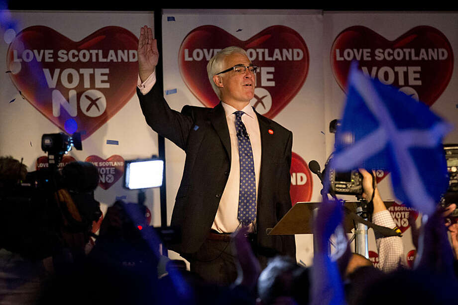 No campaigner for the Scottish independence referendum and former British finance minister Alistair Darling waves as he concludes a speech on stage after the final result was announced at a No campaign event at a hotel in Glasgow, Scotland, Friday, Sept. 19, 2014. Scottish voters have rejected independence and decided that Scotland will remain part of the United Kingdom. The result announced early Friday was the one favored by Britain's political leaders, who had campaigned hard in recent weeks to convince Scottish voters to stay. It dashed many Scots' hopes of breaking free and building their own nation. (AP Photo/Matt Dunham)