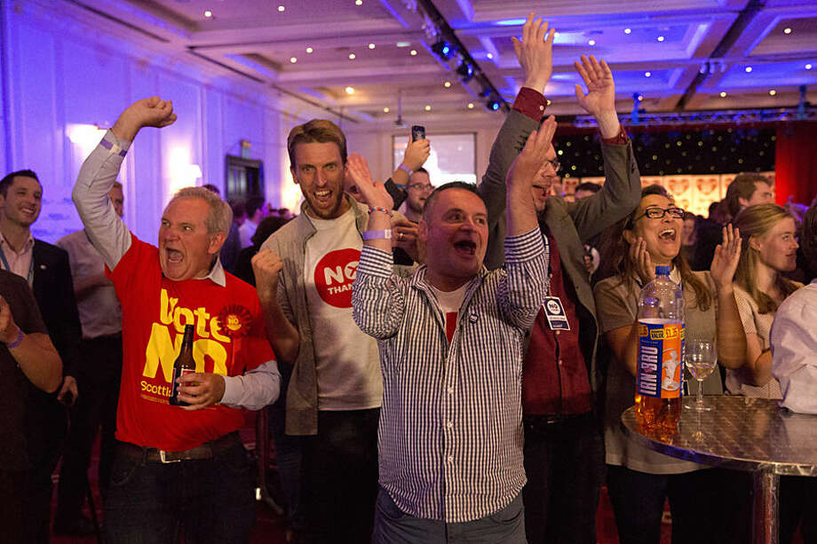 No supporters for the Scottish independence referendum celebrate an early result at a No campaign event at a hotel in Glasgow, Scotland, early Friday, Sept. 19, 2014. From the capital of Edinburgh to the far-flung Shetland Islands, Scots embraced a historic moment - and the rest of the United Kingdom held its breath - after voters turned out in unprecedented numbers for an independence referendum that could end the country's 307-year union with England. (AP Photo/Matt Dunham)