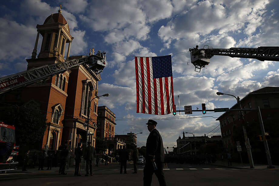 A law enforcement officer arrives for a funeral service for Pennsylvania State Trooper Cpl. Bryon Dickson, Thursday, Sept. 18, 2014, in Scranton, Pa. Dickson was killed on Friday night in an ambush shooting at the state police barracks in Blooming Grove Township. Authorities are looking for 31-year-old Eric Frein, of Canadensis, who is charged with killing one trooper and wounding another outside the barracks. (AP Photo/Matt Slocum)