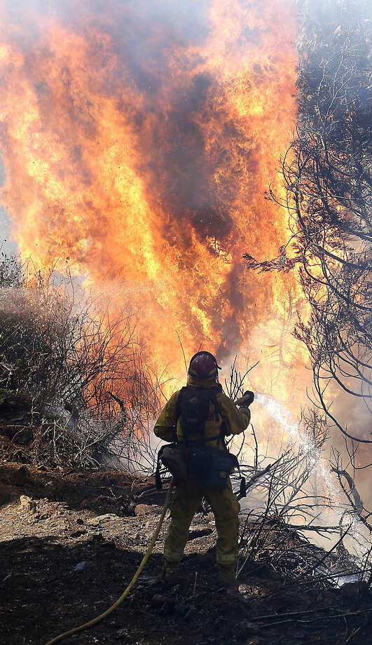 Firefighters battle a wall of flames from the King fire near Fresh Pond Fresh Pond, Calif., Wednesday, Sept. 17, 2014. The blaze that started Sunday has consumed more than 18,000 acres and is only 5 percent contained.(AP Photo/Rich Pedroncelli)