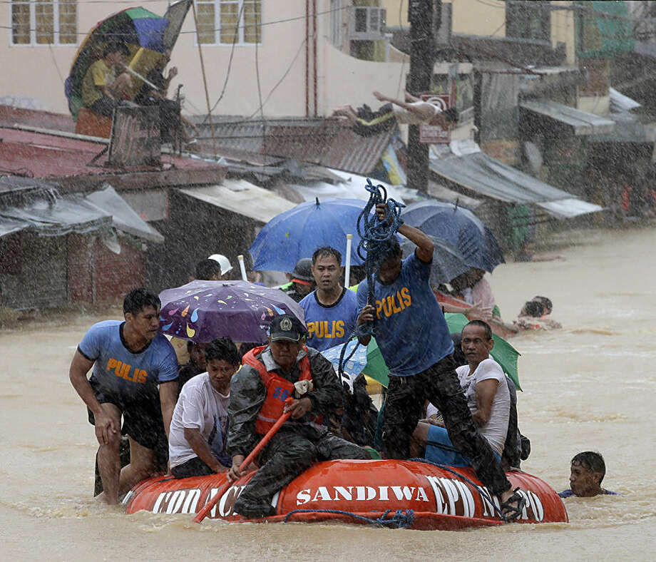 A man dives in the background as rescuers use a rubber dinghy to rescue trapped residents after continues heavy monsoon rains spawned by tropical storm Fung-Wong flooded Marikina city, east of Manila, Philippines and most parts of the metropolis Friday, Sept. 19, 2014. Heavy rains due to a storm and the seasonal monsoon caused widespread flooding Friday in the Philippine capital and nearby provinces, shutting down schools and government offices. Local authorities reported thousands were evacuated early Friday from severely inundated communities, some under rapid-flowing flood waters more than neck high.(AP Photo/Bullit Marquez)