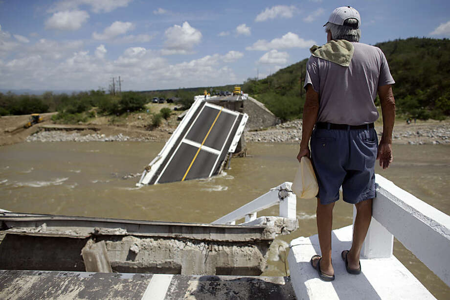 A man stands over the collapsed Aduano bridge leading to in Los Cabos, Mexico, Wednesday, Sept. 17, 2014, several days after Hurricane Odile, a category 3 storm, hit the region. President Enrique Pena Nieto's office said the federal government was working closely with state authorities on relief efforts in the areas battered by Odile, including restoring water and electricity. (AP Photo/Victor R. Caivano)