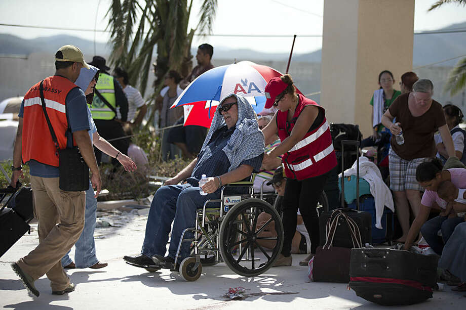An elderly man is helped by U.S. Embassy staff during the evacuation of tourists from the resort city San Jose de los Cabos, Mexico, Thursday, Sept. 18, 2014, after Hurricane Odile devastated the resort city. Authorities said they had flown 5,000 tourists out of the region by Wednesday afternoon. Officials estimated 30,000 travelers were stranded by the storm. (AP Photo/Dario Lopez-Mills)