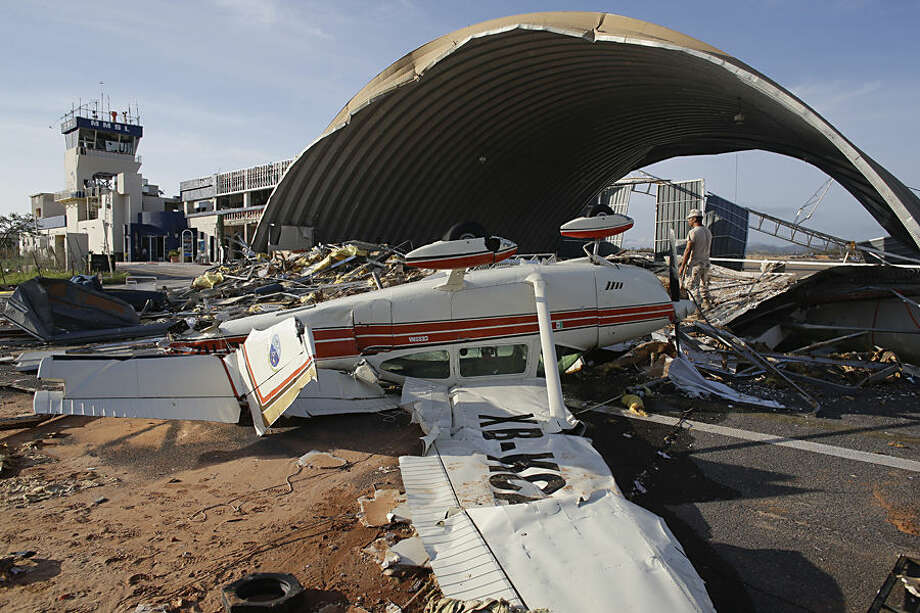 A plane destroyed by Hurricane Odile sits overturned at Cabo San Lucas airport Mexico, Wednesday, Sept. 17, 2014. Desperate locals and tourists were in survival mode in the resort area of Los Cabos on Wednesday, with electrical and water service still out three days after Hurricane Odile made landfall as a monster Category 3 storm. (AP Photo/Victor R. Caivano)