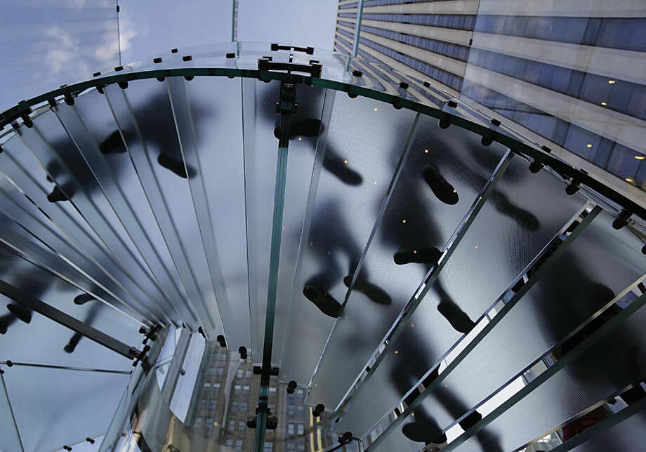 Visitors to the Apple store descend a staircase to the showroom below to purchase the iPhone 6 and 6 Plus, Friday, Sept. 19, 2014, in New York. The highly anticipated iPhone 6 and iPhone 6 Plus are being released in stores today. (AP Photo/Julie Jacobson)