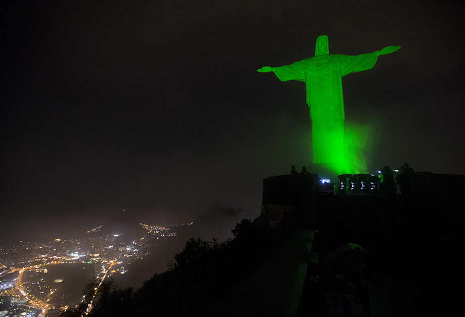 The Christ the Redeemer statue is lit up in green as a symbolic warning of the dangers of climate change, in Rio de Janeiro, Brazil, Thursday, Sept. 18, 2014. This event is in support of the Global People's Climate March, scheduled for the next Sunday, which is asking for solutions to combat global climate change, in advance of the United Nations Climate Summit to be held on September 23. (AP Photo/Silvia Izquierdo)