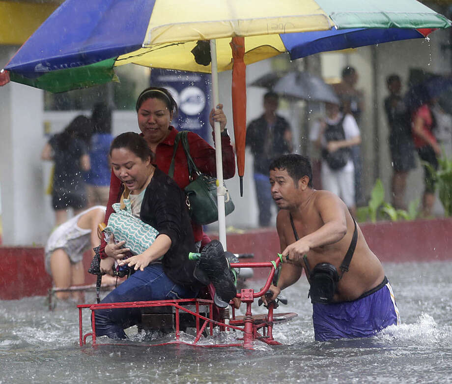 "Commuters are ferried on a three-wheeled tricycle locally known as ""sidecar"" after heavy monsoon rains spawned by tropical storm Fung-Wong flooded Manila and most parts of the metropolis Friday, Sept 19, 2014 in the Philippines. Heavy rains from a storm and the seasonal monsoon caused widespread flooding Friday in the Philippine capital and nearby provinces, shutting down schools and government offices. Local authorities reported thousands were evacuated early Friday from severely inundated communities, some with rapidly flowing waters more than neck high. (AP Photo/Bullit Marquez)"