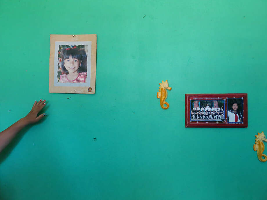 In this Sept. 15, 2014 photo, a woman who did not want to give her name for fear of reprisals, shows photographs of her daughter Erika Gomez Gonzalez on the wall of her home in Arcelia, Mexico. The woman says she witnessed her 15-years-old daughter's death when army soldiers fired first at an armed group at a grain warehouse on June 30 in the Mexican town of San Pedro Limon. According to her, one man died in the initial shootout, and the rest of the gunmen surrendered on the promise they would not be hurt. She recalled that her daughter was face down in the ground with a bullet in her leg, and was rolled over while she was still alive and shot more than half a dozen times in the chest. The mother said she arrived to the warehouse the day before the shooting in an attempt to take her daughter home, but gang members wouldn't let her. (AP Photo/Eduardo Castillo)