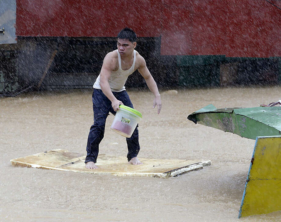 A resident balances himself on a makeshift floater as he evacuates to safety after heavy monsoon rains spawned by tropical storm Fung-Wong flooded Marikina city, east of Manila, Philippines and most parts of the metropolis Friday, Sept.19, 2014. Heavy rains due to a storm and the seasonal monsoon caused widespread flooding Friday in the Philippine capital and nearby provinces, shutting down schools and government offices.(AP Photo/Bullit Marquez)