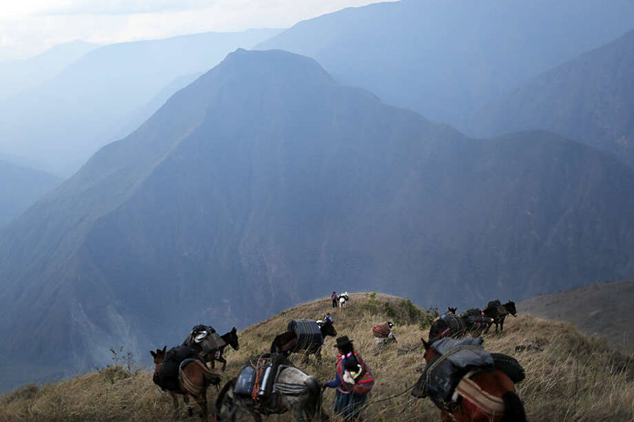 "In this Sept. 3, 2014 photo, villagers leading donkeys loaded with the working tools for anthropologists, traverse a mountain pass on a journey to help forensic investigators locate the common graves of those killed in a 1984 massacre in the Paccha village of Peru. Arriving is not easy. This rugged southeastern region known as ""Oreja de Perro,"" or Dog's Ear, lacks telephones, grocery stores and good roads. (AP Photo/Rodrigo Abd)"