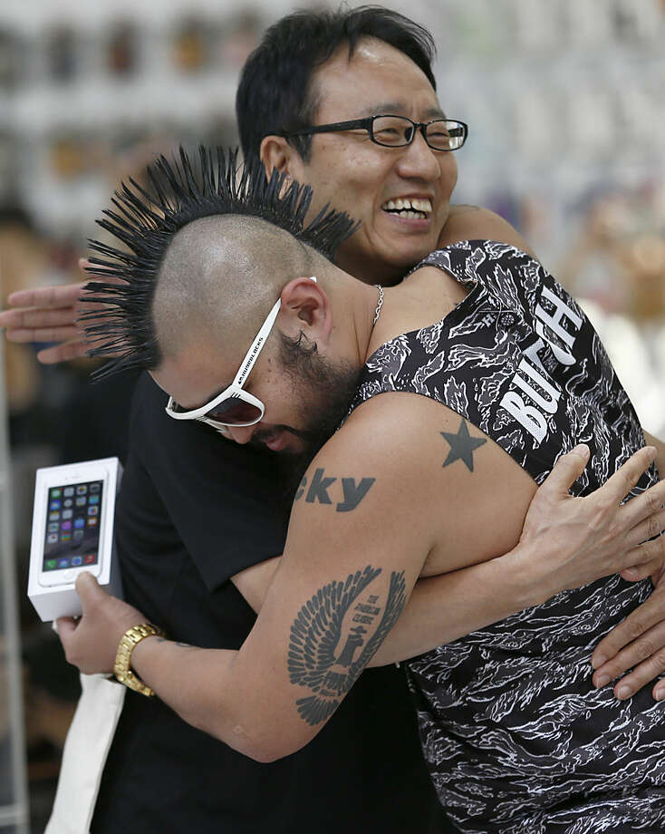 Ken Miyauchi, left, vice president of Softbank, Japanese mobile phone company hugs the first customer of iPhone 6 during a ceremony to mark the first day of sales of the new Apple iPhone 6 and 6 Plus at a store in Tokyo Friday, Sept. 19, 2014. (AP Photo/Shizuo Kambayashi)