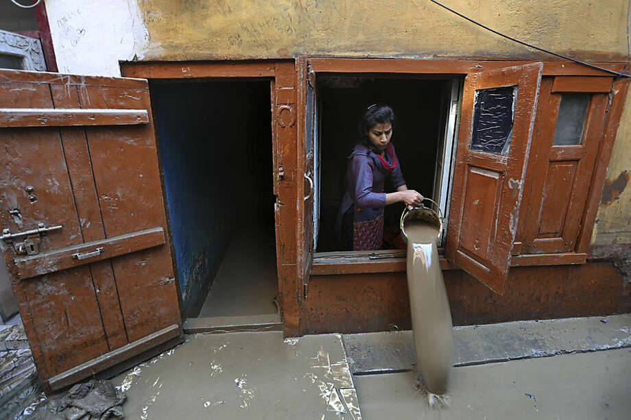 A Kashmiri woman drains muddy water from her flood damaged house in Srinagar, Indian-controlled Kashmir, Thursday, Sept.18, 2014. The floods engulfed much of Kashmir two weeks ago, leaving hundreds of thousands of people homeless in both the Indian- and Pakistani-administered areas of the disputed territory. (AP Photo/Dar Yasin)