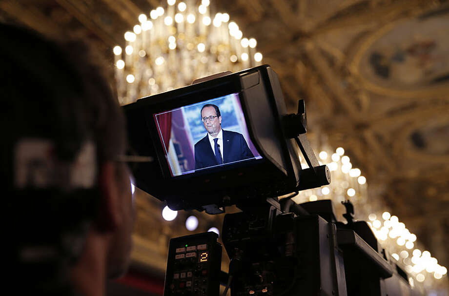 French President Francois Hollande appears on the TV monitor as he delivers his speech during a press conference at the Elysee Palace, Thursday, Sept.18, 2014. Hollande said he agreed to Iraq's request for air support at a meeting of his top defense and security advisers earlier Thursday. (AP Photo/Christophe Ena)