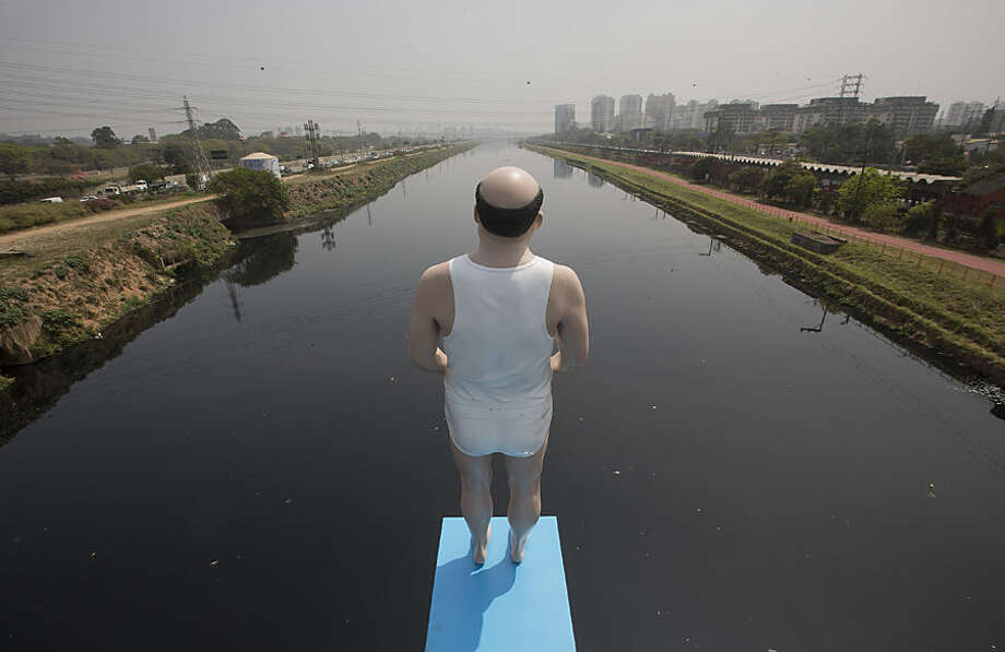 An art installation by Brazilian artist Eduardo Srur made with a life-size mannequin stands over the highly polluted Pinheiros River in Sao Paulo, Brazil, Thursday, Sept. 18, 2014. Srur says his work aims to warn people about the pollution in the city's rivers. (AP Photo/Andre Penner)