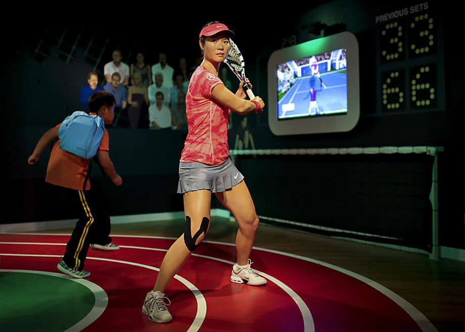A student plays with a motion-controlled tennis games near a wax figure of Chinese tennis player Li Na on display at the Madame Tussauds Museum in Beijing, China Friday, Sept. 19, 2014. Li Na, a two-time Grand Slam champion from China who took tennis in Asia to a new level, has retired due to recurring knee injuries. (AP Photo/Andy Wong)