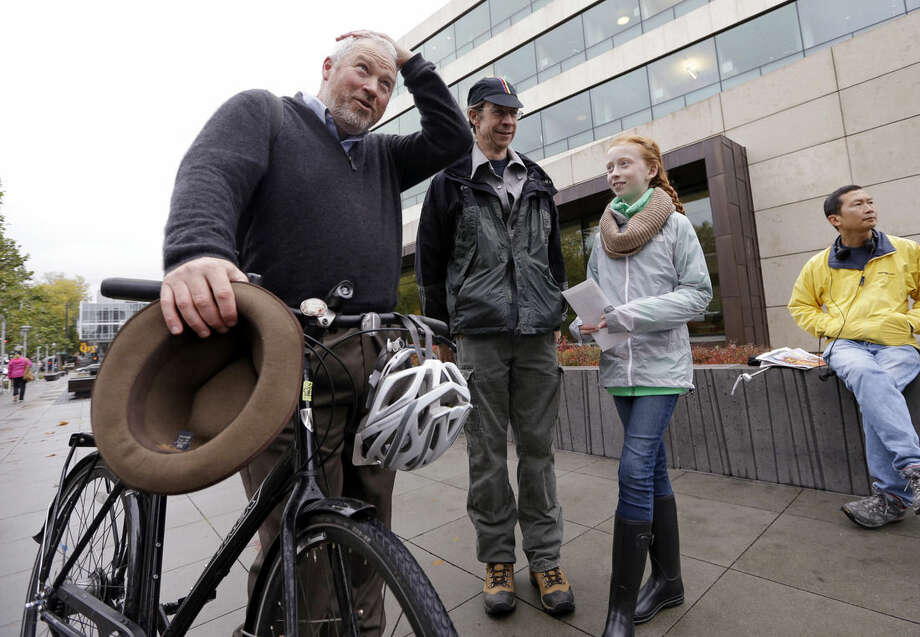 In this photo taken Wednesday, Oct. 28, 2015, teenage environmental activists Wren Wagenbach, 14, second right, stands with her father, Mike Wagenbach, as they talk with former mayor Mike McGinn before a rally in Seattle. Wren Wagenbach is one of eight youth activists who petitioned Washington state last year to adopt stricter science-based regulations to protect them against climate change. (AP Photo/Elaine Thompson)
