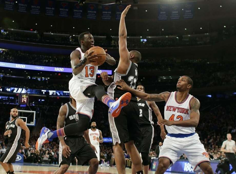 New York Knicks' Jerian Grant (13) drives past San Antonio Spurs' Boris Diaw (33) as teammate Lance Thomas, right, watches during the first half of an NBA basketball game Monday, Nov. 2, 2015, in New York. (AP Photo/Frank Franklin II)