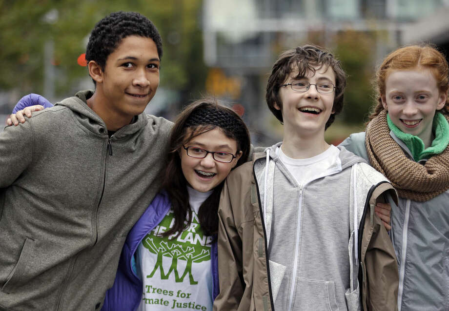 In this photo taken Wednesday, Oct. 28, 2015, teenage environmental activists Aji Piper, left, 15, Lara Fain, 13, Gabriel Mandell, 13, and Wren Wagenbach, 14, playfully pose for a photo after a rally they spoke at in Seattle. The four are among eight youth activists who petitioned Washington state last year to adopt stricter science-based regulations to protect them against climate change. (AP Photo/Elaine Thompson)