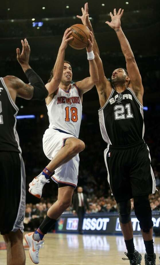 New York Knicks' Sasha Vujacic (18), of Slovenia, drives past San Antonio Spurs' Tim Duncan (21) during the first half of an NBA basketball game Monday, Nov. 2, 2015, in New York. (AP Photo/Frank Franklin II)