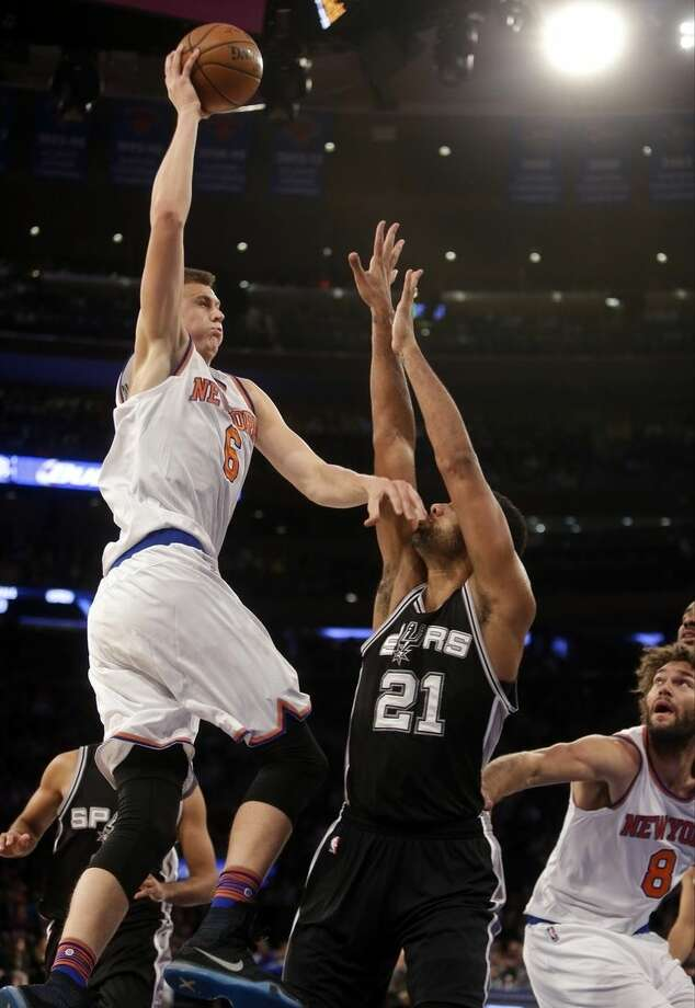 New York Knicks' Kristaps Porzingis (6), of Latvia, shoots over San Antonio Spurs' Tim Duncan (21) during the first half of an NBA basketball game Monday, Nov. 2, 2015, in New York. (AP Photo/Frank Franklin II)