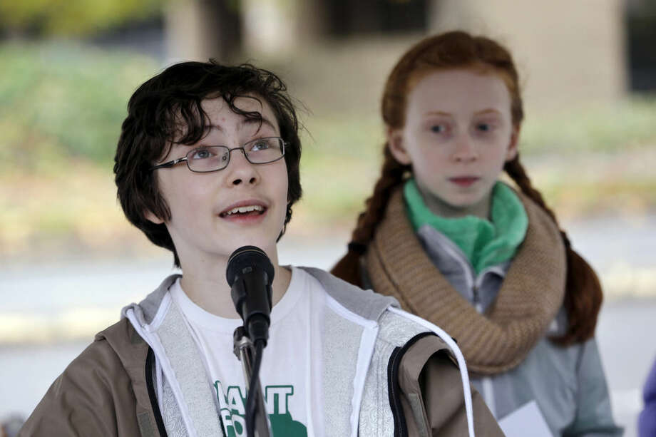 In this photo taken Wednesday, Oct. 28, 2015, teenage environmental activist Gabriel Mandell, left, 13, speaks at a rally as and Wren Wagenbach, 14, looks on in Seattle. The two are among eight youth activists who petitioned Washington state last year to adopt stricter science-based regulations to protect them against climate change. (AP Photo/Elaine Thompson)