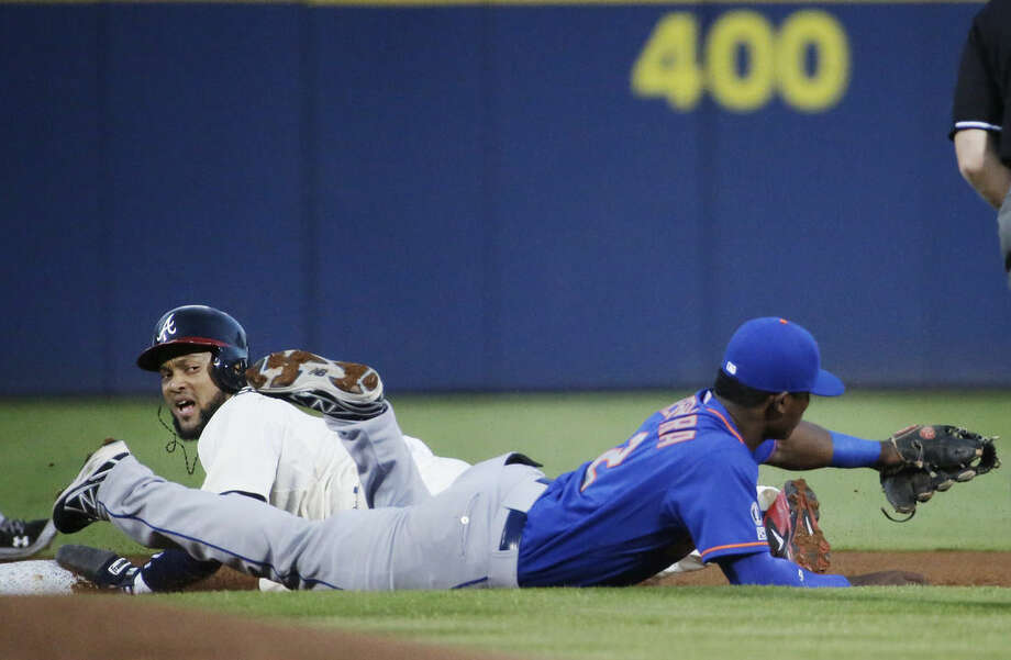 Atlanta Braves' Emilio Bonifacio, left, looks up after beating the throw to New York Mets' Dilson Herrera to steal second base in the first inning of a baseball game, Saturday, Sept. 20, 2014, in Atlanta. (AP Photo/David Goldman)