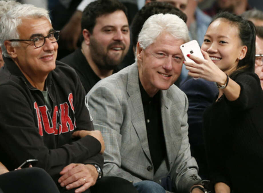 Milwaukee Bucks owner Marc Lasry, left, smiles as a spectator takes a selfie with former President Bill Clinton, center, during the first half of an NBA basketball game between the Brooklyn Nets and the Milwaukee Bucks, Monday, Nov. 2, 2015, in New York. (AP Photo/Kathy Willens)