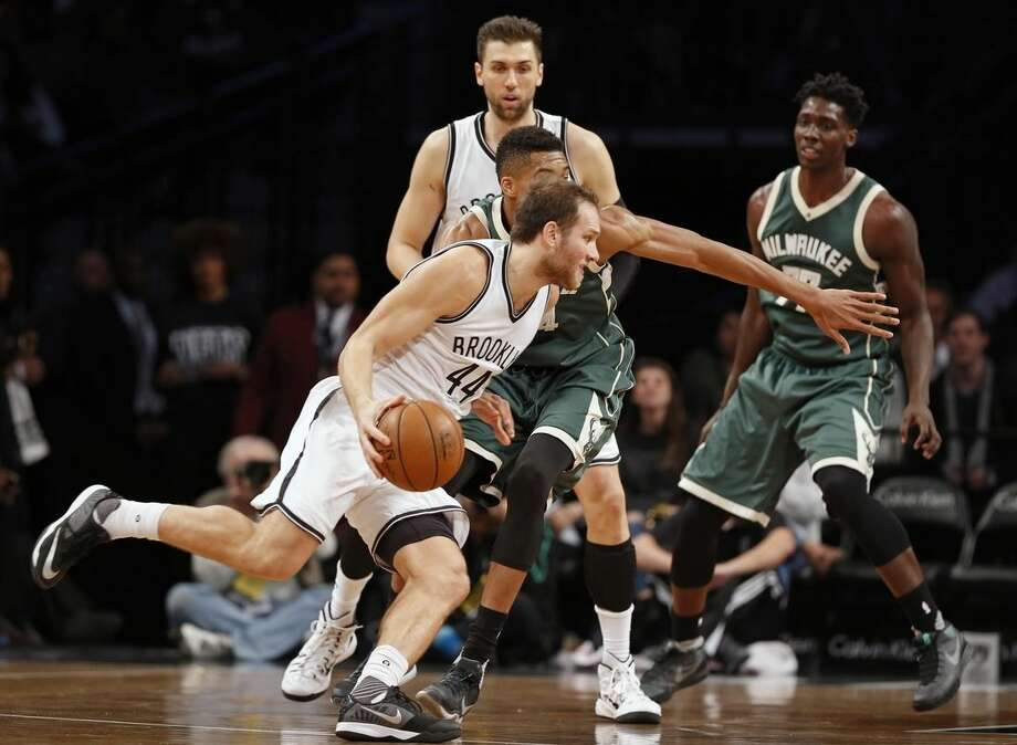 Brooklyn Nets guard Bojan Bogdanovic (44) drives past in Milwaukee Bucks forward Giannis Antetokounmpo as Johnny O'Bryant III watches in the first half of an NBA basketball game, Monday, Nov. 2, 2015, in New York. (AP Photo/Kathy Willens)
