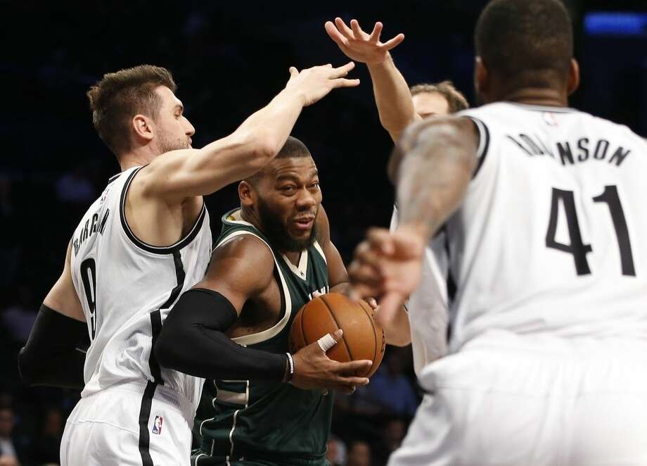 Milwaukee Bucks center Greg Monroe, center, drives through Brooklyn Nets center Andrea Bargnani, left, as Brooklyn Nets forward Thomas Robinson (41) defends in the first half of an NBA basketball game Monday, Nov. 2, 2015, in New York. (AP Photo/Kathy Willens)
