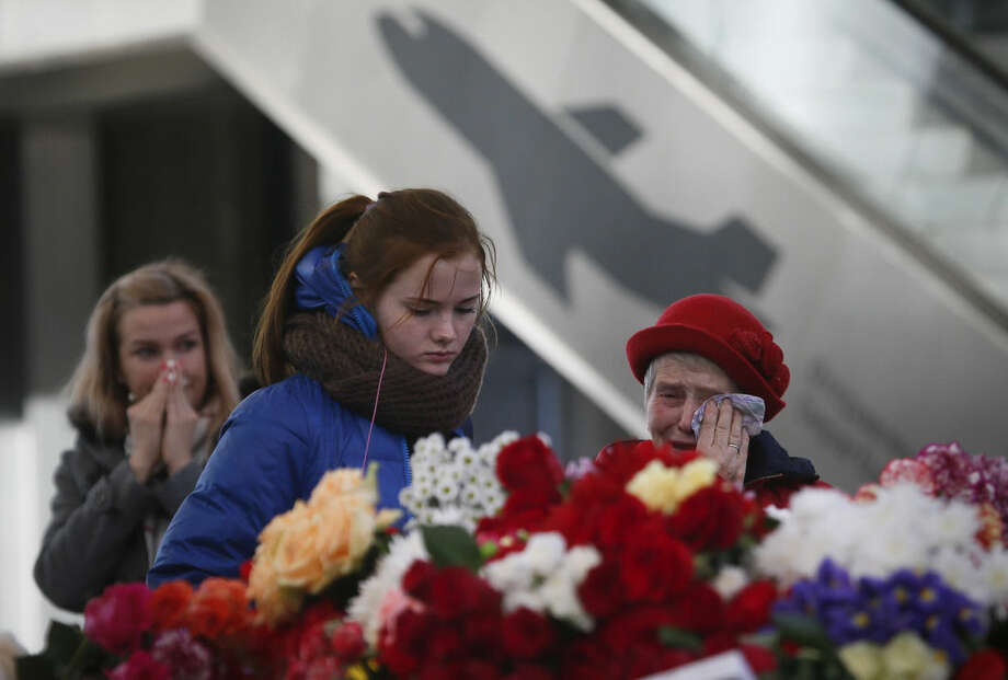 People react, at an entrance of Pulkovo airport during a day of national mourning for the victims of the plane crash, outside St. Petersburg, Russia, Tuesday, Nov. 3, 2015. In a massive outpouring of grief, thousands of people flocked to St. Petersburg's airport, laying flowers, soft toys and paper planes next to the pictures of the victims of the crash of a passenger jet in Egypt that killed all 224 on board in Russia's deadliest air crash to date. (AP Photo/Dmitry Lovetsky)