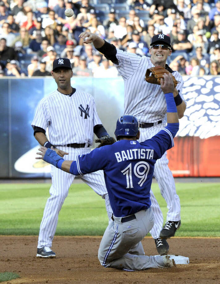 Toronto Blue Jays' Jose Bautista (19) is out at second as New York Yankees second baseman Stephen Drew throws the ball to first to complete the double play on Dioner Navarro as Yankees' Derek Jeter, left, looks on during the third inning of a baseball game Saturday, Sept. 20, 2014, at Yankee Stadium in New York. (AP Photo/Bill Kostroun)
