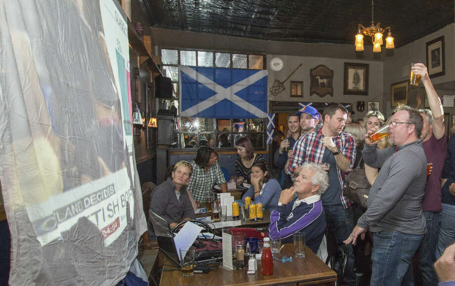 In this Thursday, Sept. 18, 2014 photo, patrons of the Duke of Perth, react as they watch vote results come in on a referendum on Scotland becoming an independent state during a live feed of Scottish television coverage projected on the wall of the pub. The pub is Scottish-owned, and many of the patrons are from Scotland. Scottish voters resoundingly rejected independence, deciding to remain part of the United Kingdom after a historic referendum that shook the country to its core. (AP Photo/Teresa Crawford)