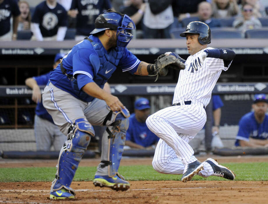 New York Yankees' Derek Jeter, right, scores on a single by Brian McCann as Toronto Blue catcher Dioner Navaro waits for the ball during the third inning of a baseball game Saturday, Sept. 20, 2014, at Yankee Stadium in New York. (AP Photo/Bill Kostroun)