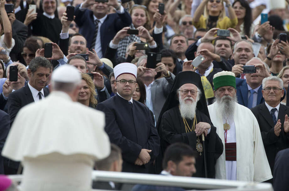 Albanian religious leaders look at Pope Francis arriving for a Mass in mother Teresa square, Tirana, Sunday, Sept. 21, 2014. Pope Francis arrived Sunday in Albania on his first European trip, designed to highlight the Balkan nation's path from a brutal communist state where religion was banned to a model of Christian-Muslim coexistence for a world witnessing conflict in God's name. (AP Photo/Alessandra Tarantino)