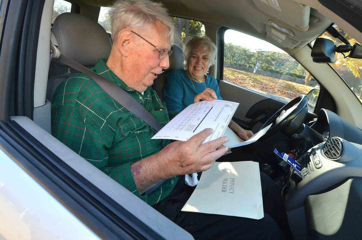 Hour Photo/Alex von Kleydorff Because of limited mobility Alex and Dorothy Forbes were able to vote curbside by having Assistant Registrars Jessica Blackwell and Chris Perone check them in with ID's and bring them the ballots during voting at Marving Elementary School on Tuesday
