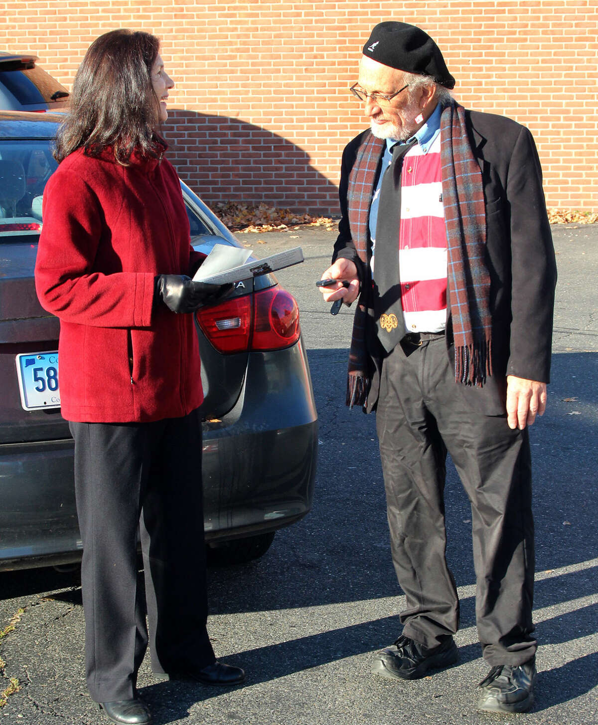 Hour photo/Chris Bosak Democratic candidate for First Taxing District Treasurer Elsa Peterson Obuchowski gets an early voter turnout update from Assistant Democratic Registrar Bob Sodaro on Tuesday morning at St. Mary's Community Hall on West Avenue in Norwalk.